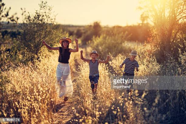 Children running on old dirt road in Tuscany, Italy