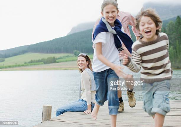 Children running on pier by lake