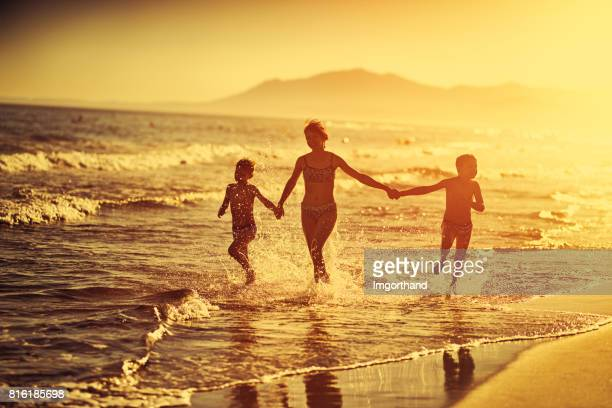 Children running on sandy beach on costa del sol beach, Marbella, Spain