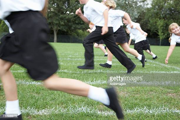 Children (5-8) running on sports field, low section