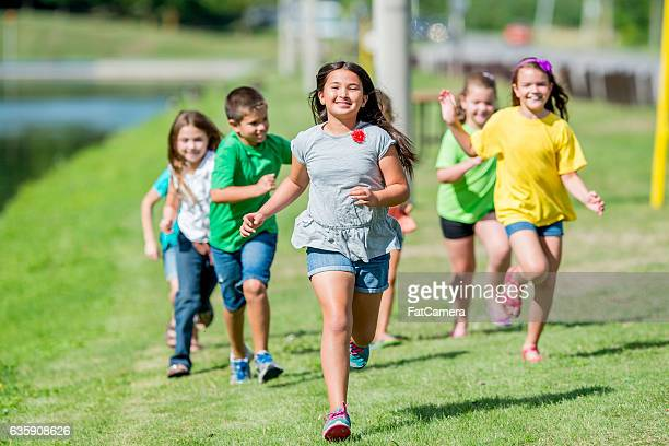 children running outside on a sunny day - kids playing tag stock photos and pictures
