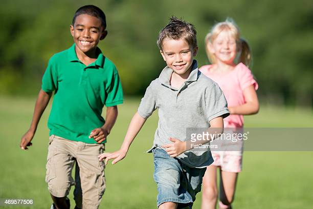children running outside - polo shirt stock pictures, royalty-free photos & images