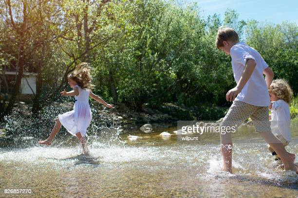 children running through and kicking water - river bed stock photos and pictures