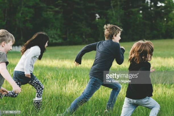 children running through grassy field - achtervolging begrippen stockfoto's en -beelden