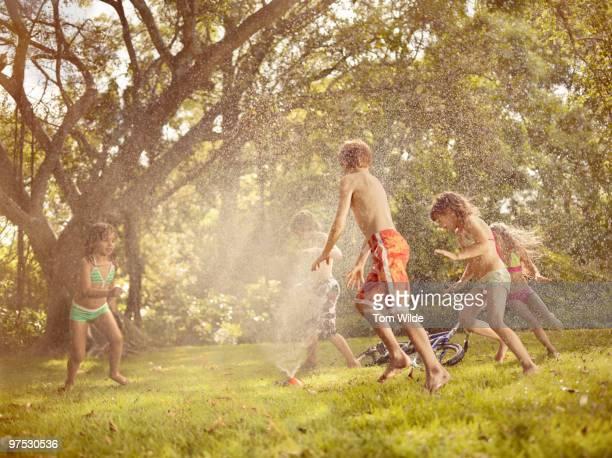 Children running through sprinkler in garden