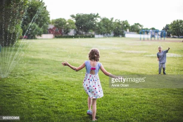 Children running through sprinkler
