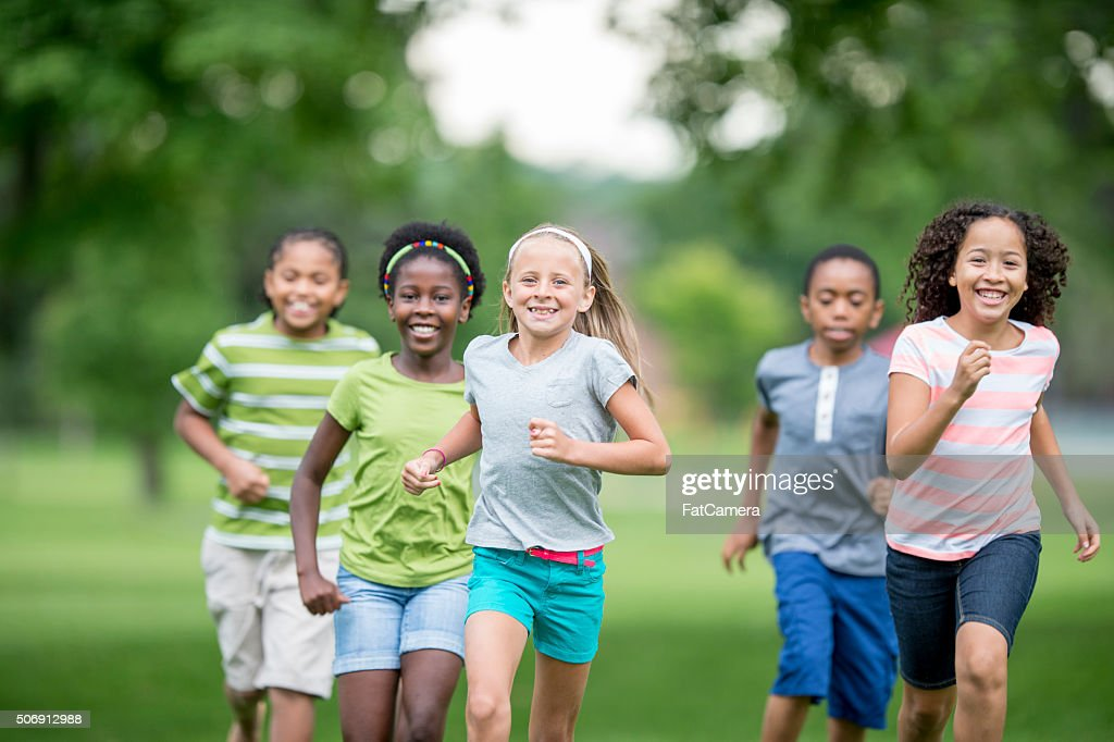Niños corriendo a través de la hierba : Foto de stock