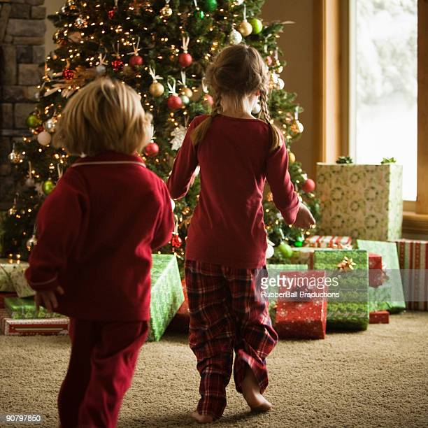 children running to presents on christmas morning - orem utah stock pictures, royalty-free photos & images