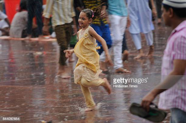 Children running to shield themselves from rains near Jama Masjid on July 1 2016 in New Delhi India The capital received its first Monsoon rains...