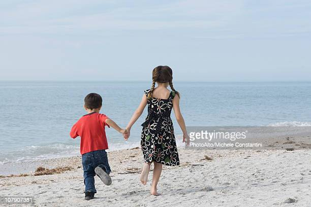 Children running together at the beach, holding hands