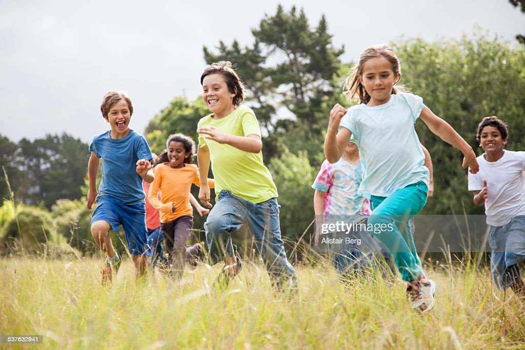 Children running together in a park : Stock Photo