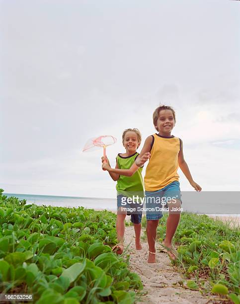 children running together on beach - hapuna beach stock photos and pictures