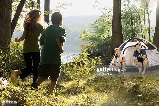 Children running towards parents at campsite in nature