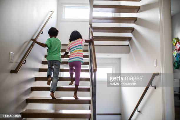children running up staircase at home - railing stock pictures, royalty-free photos & images