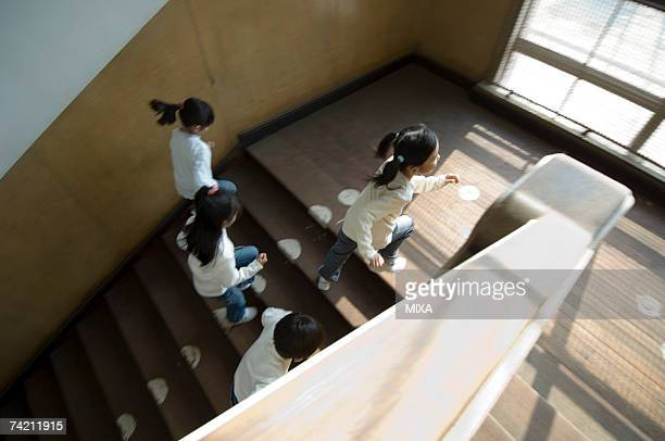 Children running up staircase