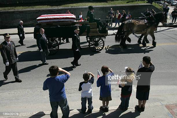Children salute as the caisson carrying Providence Police Detective Sgt James Allen passes them on Cranston Street en route to St Ann Cemetery