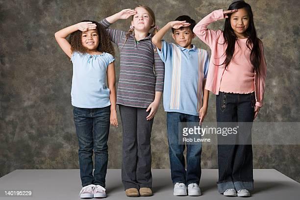 Children (6-7, 8-9) saluting, studio shot