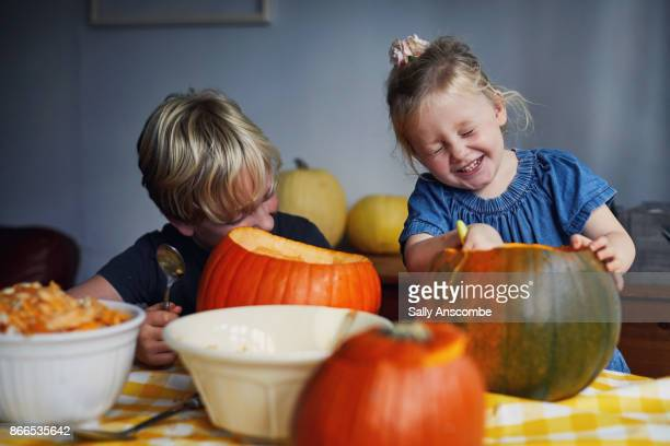 children scooping out pumpkins - pumpkin stock pictures, royalty-free photos & images