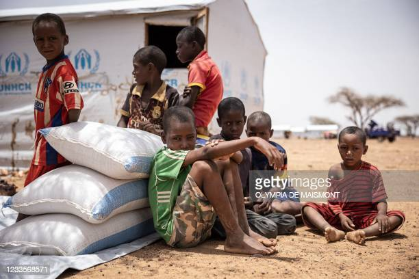 Children seat by their shelter in Goudebou, a camp that welcomes more than 11,000 Malian refugees in northern Burkina Faso, on International Refugee...