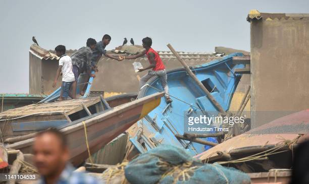 Children seen sharing foods as they stand on a damaged boat at Penthakota fishermen colony on May 4 2019 in Puri India At least 12 people are...