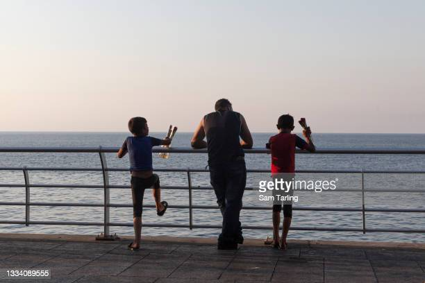 Children selling roses rest by the sea in Beirut, Lebanon, on August 13, 2021. Lebanon's economic crisis has resulted in a surge of children going...