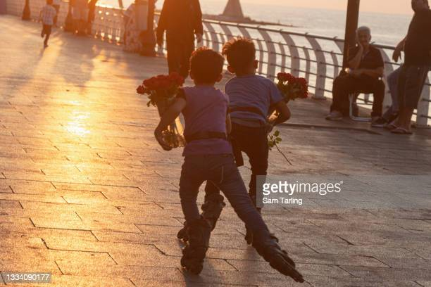 Children selling roses use roller-skates by the sea in Beirut, Lebanon, on August 13, 2021. Lebanon's economic crisis has resulted in a surge of...