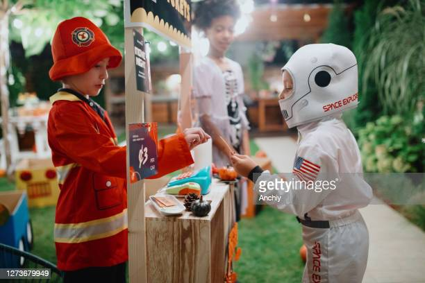 children selling tickets from ticket stand to their friends at drive-in movie party ticket stand - scaredastronaut stock pictures, royalty-free photos & images