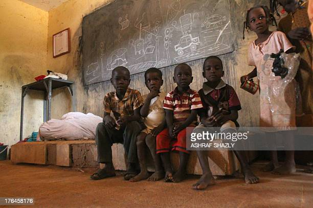 Children shelter in a classroom following heavy rains in Omdurman some 30 kilometers northwest of the Sudanese capital Khartoum on August 13 2013 The...