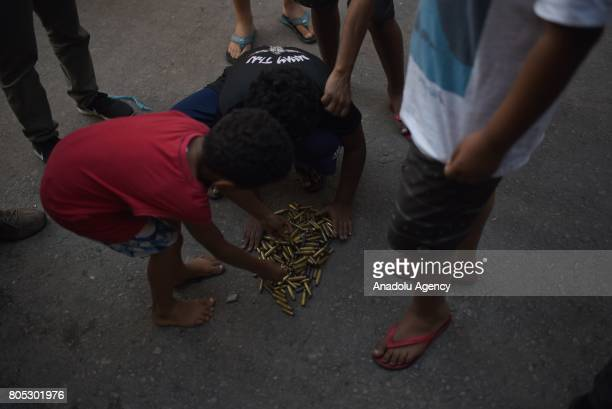 Children show spent bullet casings after a police operation at the Mangueira favela in Rio de Janeiro Brazil on June 30 2017