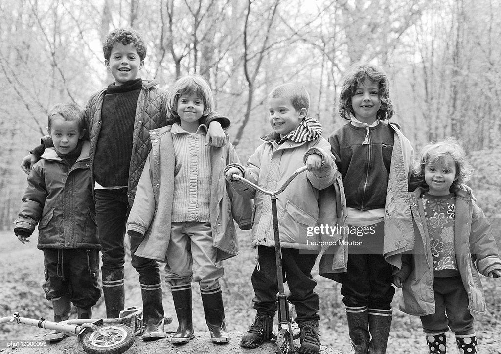 Children side by side in forest, b&w : Stockfoto