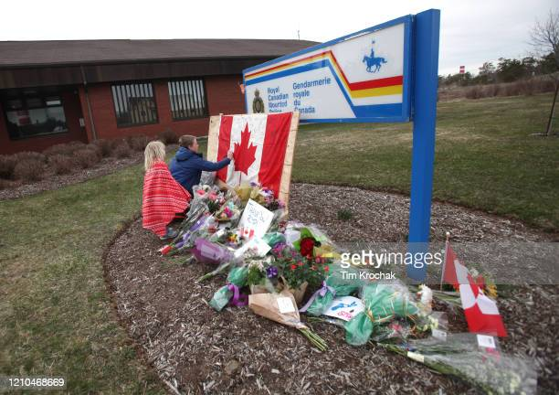 Children sign a Canadian flag at an impromptu memorial in front of the RCMP detachment April 20 2020 in Enfield Nova Scotia Canada It was the home...