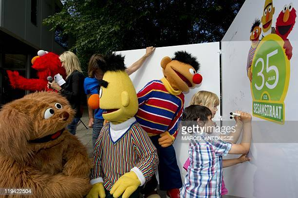 Children sign a wall as they mark the 35th anniversary of Sesame Street flanked by Sesame Street characters Elmo Tommie Bert and Ernie at the Dalton...