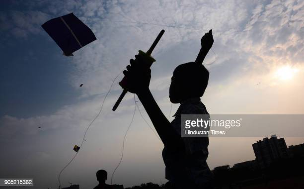"Children silhouetted against the sky as they fly kite ahead of ""Makar Sankranti"", on January 12, 2018 in Pune, India. Makara Sankranti is a festival..."