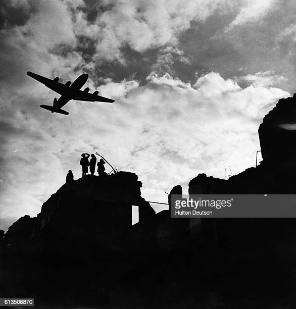 Children silhouetted amid the ruins of Berlin look to the skies as an RAF aircraft passes overhead during the Soviet blockade of the city Germany 1948