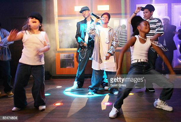 Children sing and dance along side the new wax figure of R B singer Usher during a competition to launch the Usher Interactive Experience at Madame...