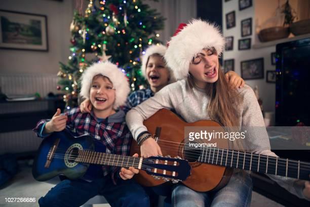 kinder singen weihnachtslieder weihnachtsbaum - singen stock-fotos und bilder