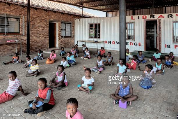 Children sit as they wait for the daily food distribution in the Tembisa informal settlement, Johannesburg, on April 24, 2020. - Despite the promise...