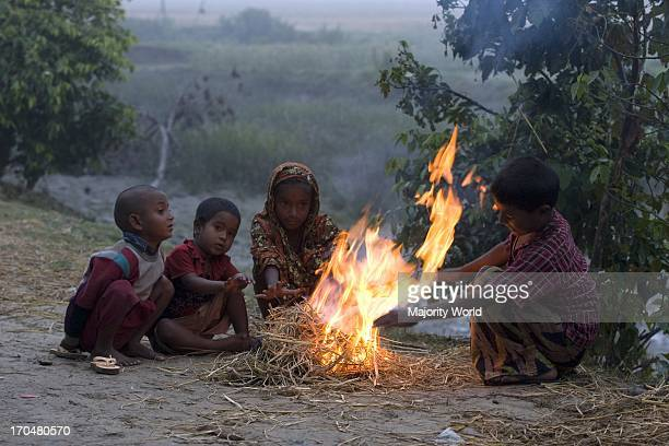 Children sit by a fire to warm themselves as winter cold sets in Nijhum Dwip a cluster of islands emerged in the early 1950s in the shallow estuary...