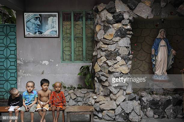 Children sit by a Virgin Mary statue at the Mother Teresa orphanage in Old Dhaka on November 17 2009 The heads of twoyearold conjoined twins Trishna...