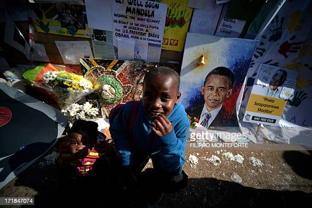 Children sit by a wall of messages and flowers left for former South African President Nelson Mandela outside the MediClinic Heart hospital in...