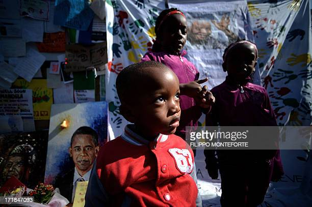Children sit by messages and flowers left for former South African President Nelson Mandela outside the MediClinic Heart hospital in Pretoria where...