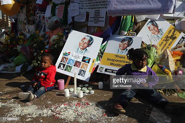 Children sit in front of a wall covered with messages and flowers for former South African President Nelson Mandela outside the MediClinic Heart...