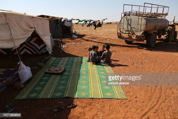Children sit in front of their tent at a camp built by displaced people near a Turkish observation point after they were forced to leave the camps in...