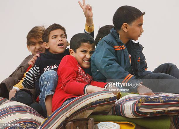 Children sit in the back of a civilian truck packed with bags as they drive down a highway during a hasty withdrawal April 7, 2011 in Ajdabiyah,...