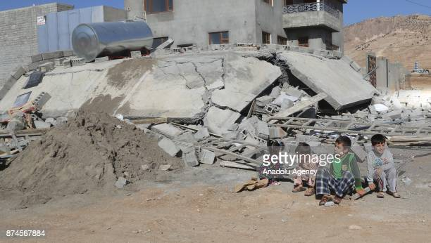 Children sit near a debris at Darbandikhan district of Suleymaniyah after an earthquake measuring 73 on the Richter scale rocked northern Iraq and...