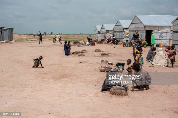 Children sit near their parents as they cook meals in one of the IDP camps in Pulka on August 1, 2018. - As the presidential race heats up ahead of...