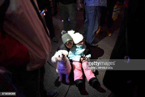 Children sit next to a dog during a protest against government and corruption in the front of the Romanian Government headquarters in Bucharest on...