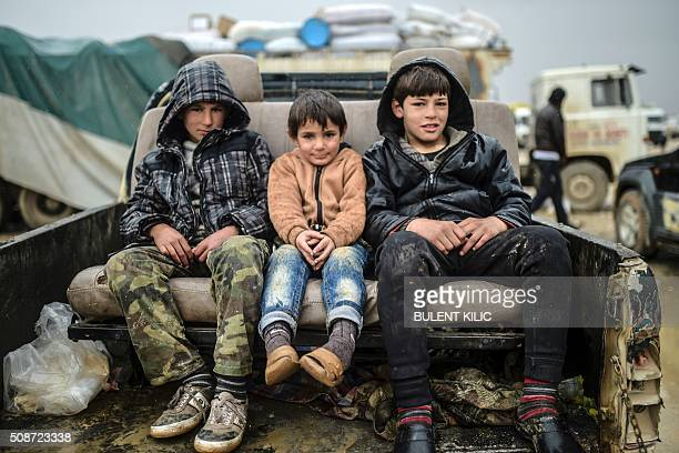 TOPSHOT Children sit on a car as Syrians fleeing the northern embattled city of Aleppo wait on February 6 2016 in Bab alSalama near the city of Azaz...