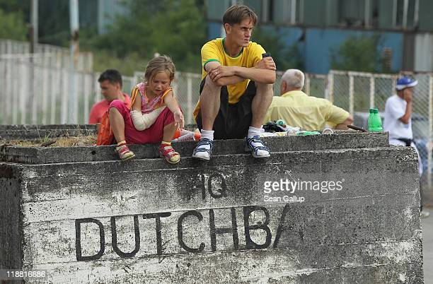 Children sit on a concrete block outside the former base of Dutch UN soldiers following the mass funeral for 613 newlyidentified victims of the 1995...