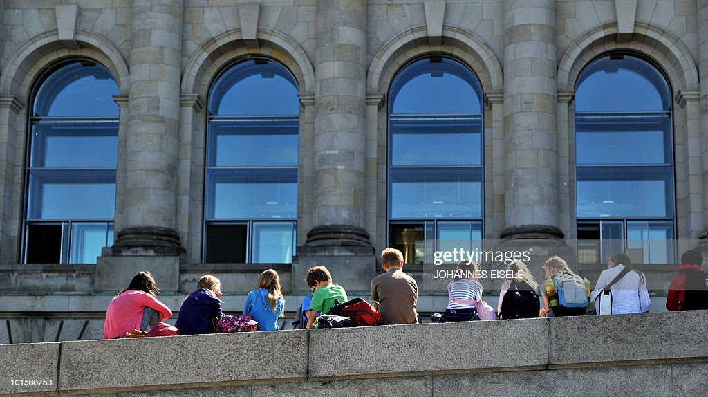 Children sit on a wall in front of the Reichstag (lower house of parliament) on June 3, 2010 in Berlin. Summer finanlly starts in Germany on June 3, 2010, after weeks of cold and rainy weather.